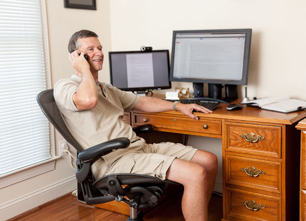 Senior caucasian man working from home in shorts with desk with two monitors