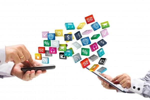 Manos-tocando-un-celular-y-una-tablet-y-saliendo-iconos-de-estos-dispositivos